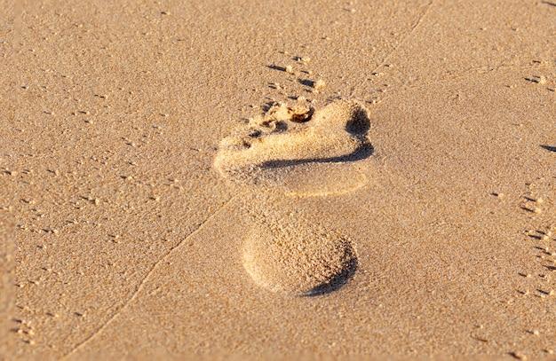 Close-up de uma pegada na areia.