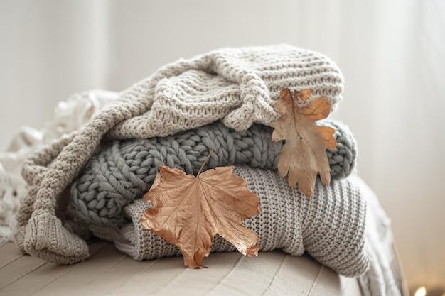 Close-up de uma pilha de camisolas de malha em um fundo desfocado.