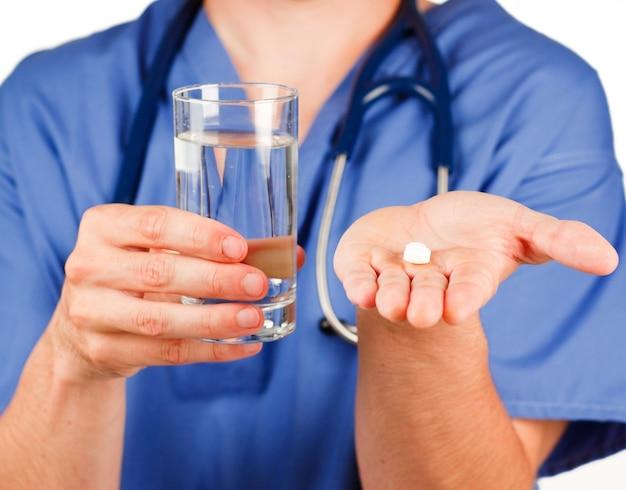 Close-up de uma pílula e um copo de água