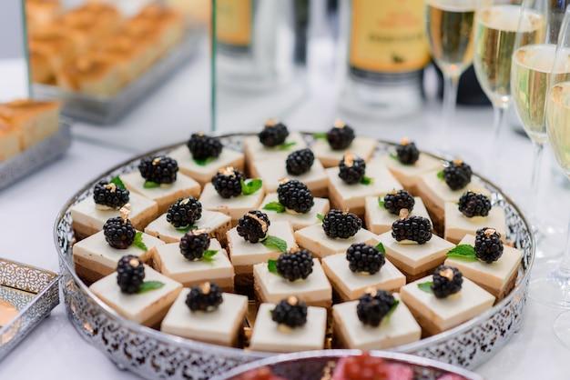 Close up de uma porção de sobremesas de mousses bege decoradas com amoras