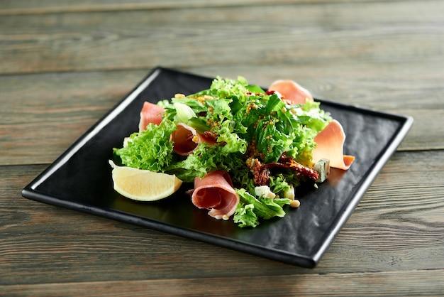 Close up de uma salada light, que inclui fatias de presunto, folhas de alface