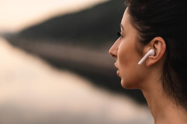 Close-up de uma senhora atraente usando fones de ouvido sem fio enquanto descansa ao ar livre enquanto sonha