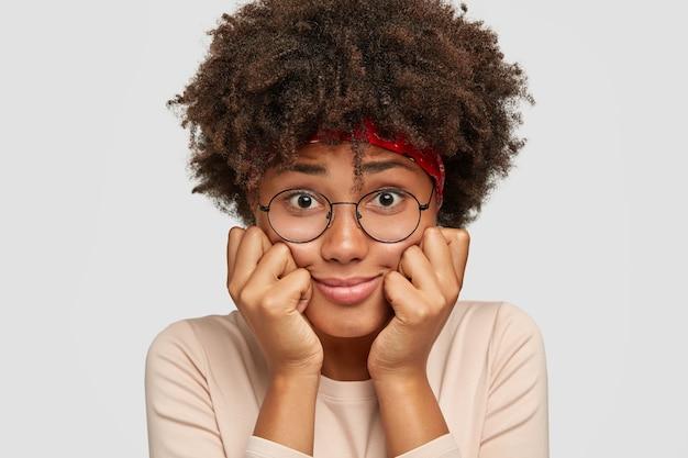 Close up de uma senhora negra envergonhada surpreendendo com uma expressão facial abatida
