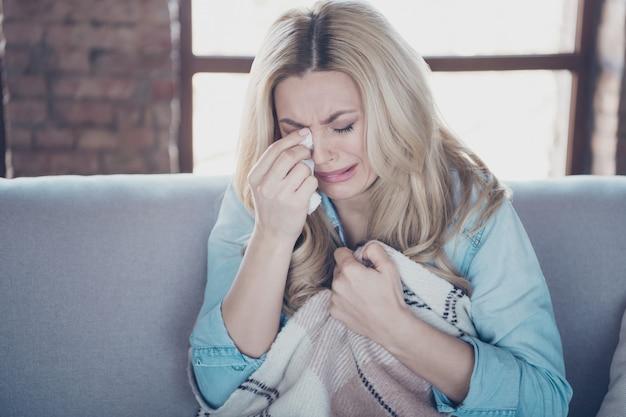 Close-up de uma senhora sentada no divã, enxugando lágrimas e chorando