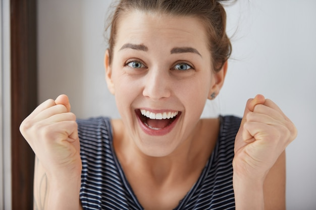 Close-up de uma sorridente garota europeia de olhos azuis cerrando os punhos em alegria sem fim. emoções positivas e sentimento de triunfo merecido fazem com que uma mulher encantadora fique linda na parede branca.