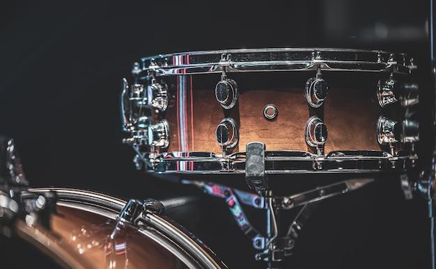 Close-up de uma tarola, instrumento de percussão em um fundo escuro.