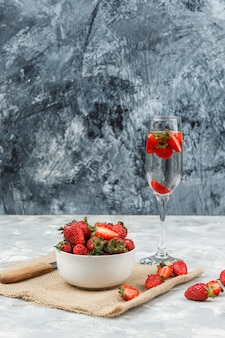 Close-up de uma tigela de morangos em um pedaço de saco com um copo de bebida na superfície de mármore branco e azul escuro. vertical