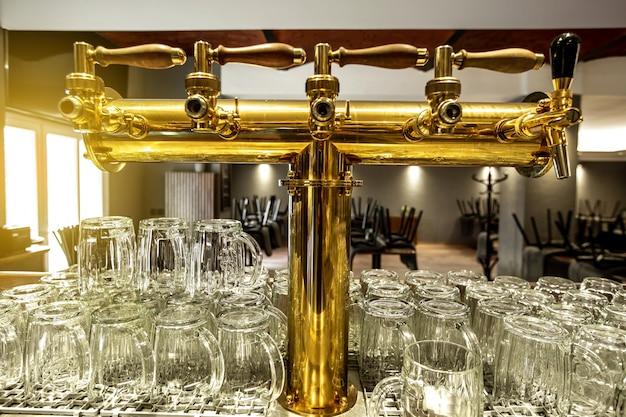 Close up de uma torneira de cerveja ou torneira com grande arrenge de um copo vazio no bar ou pub, conceito de restaurante
