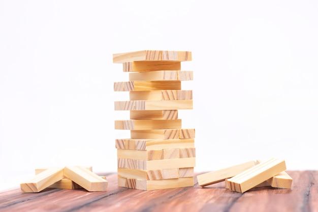 Close-up de uma torre de madeira clara feita de blocos. jogo de tabuleiro em cima da mesa. atividade para estratégia e concentração. conceito de negócios