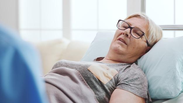 Close-up de uma velha doente deitada na cama conversando com um assistente, por cima do ombro