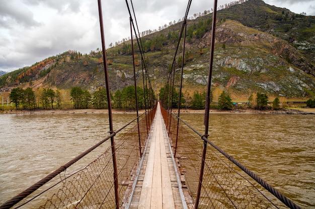 Close-up de uma velha ponte de madeira sobre um rio de montanha, na parte de trás de árvores verdes coníferas e uma montanha em um dia quente de verão