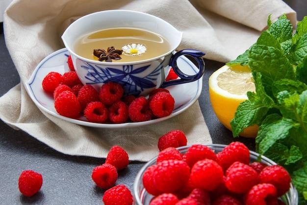 Close-up de uma xícara de chá de camomila com limão, folhas de hortelã, framboesas em pires no pano