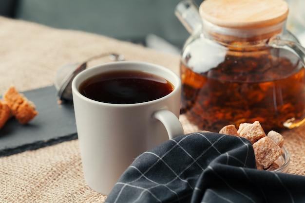 Close up de uma xícara de chá e doces na mesa de madeira