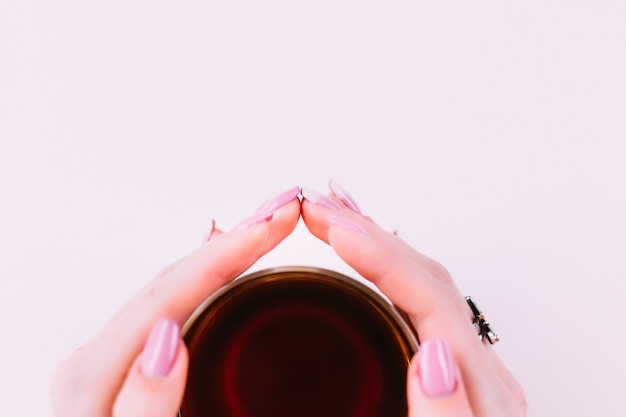 Close-up de uma xícara de chá na parte inferior da foto e os dedos da menina em volta da xícara