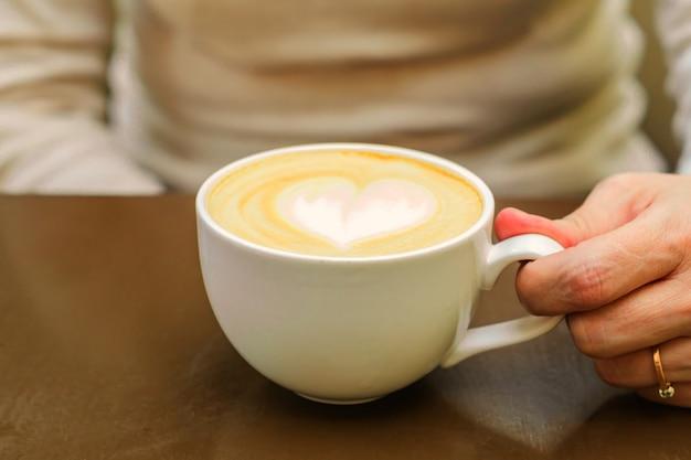 Close-up de uma xícara grande de cappuccino acabado de fazer com espuma macia e açúcar mascavo e coração de desenho por barista