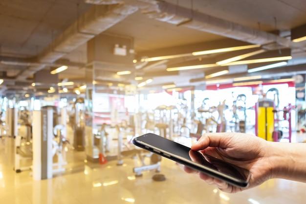 Close-up de uso feminino mão segurando imagens borradas de smartphone toque de desfoque abstrato de interior de ginásio de esporte desfocado e clube de saúde fitness com equipamento de exercícios esportivos fundo de desfoque de ginásio.