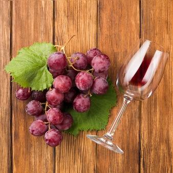 Close up de uvas e copo de vinho vermelho
