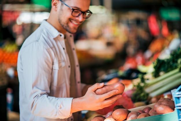 Close-up de vegetais de compra ocasionais felizes de um homem novo no mercado local.