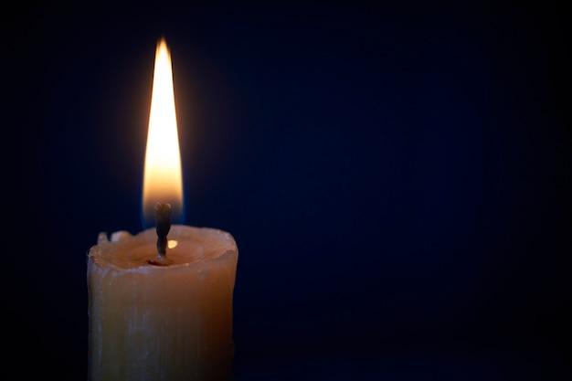 Close-up de vela branca acesa no escuro, fogo de vela