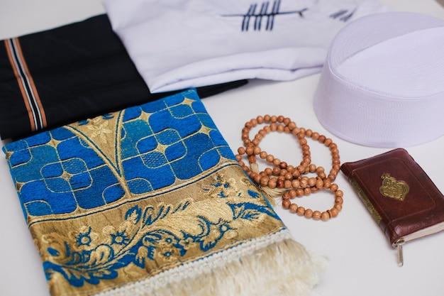 Close up de vestido tradicional muçulmano e contas de oração com tapete de oração e livro sagrado al quran. há uma letra árabe que significa o livro sagrado