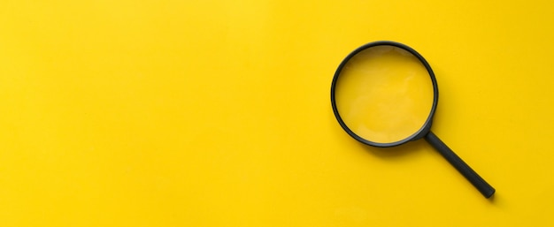 Close-up de vidro de lupa em fundo amarelo