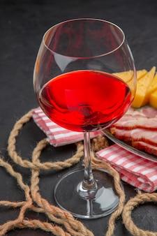 Close up de vinho tinto em uma taça de vidro e queijo fatiado em uma toalha vermelha listrada em uma mesa preta