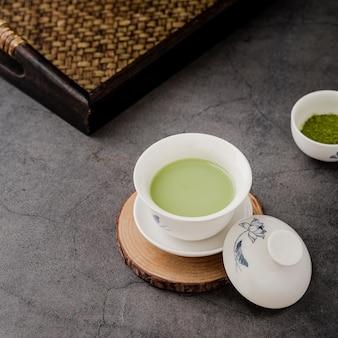 Close-up de xícara de chá matcha na pousa-copos e bandeja