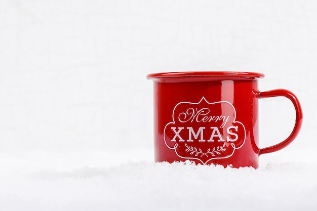 Close up de xícara vermelha com palavras feliz natal na neve