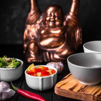 Close-up de xícaras de legumes com estátua