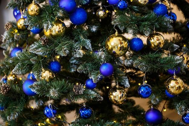 Close-up decorado da árvore de natal. bolas azuis e douradas e luzes de guirlanda. bolas de natal na árvore. feriado de inverno ano novo e natal