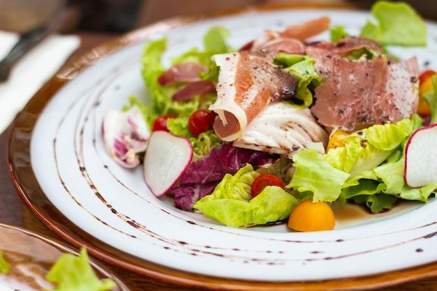 Close up defumado salada de pato em chapa branca em cima da mesa