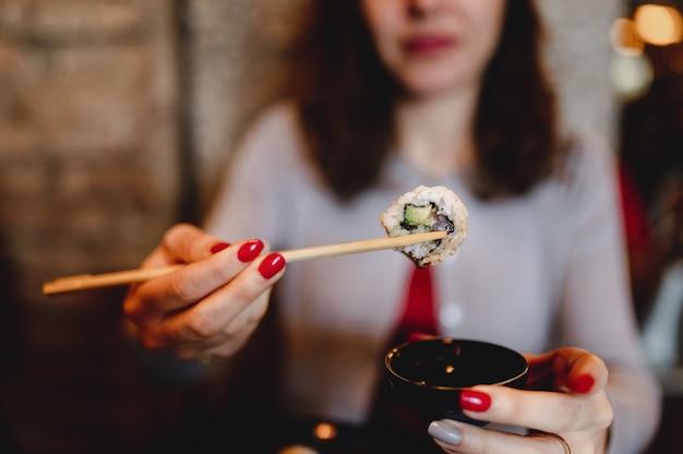 Close-up desfocado de mulher segurando o tradicional sushi roll de salmão japonês com abacate colocado entre os pauzinhos