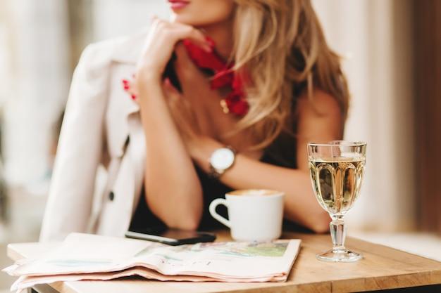 Close-up desfocado retrato de mulher elegante usando lenço vermelho e relógio de pulso com um copo de vinho em primeiro plano