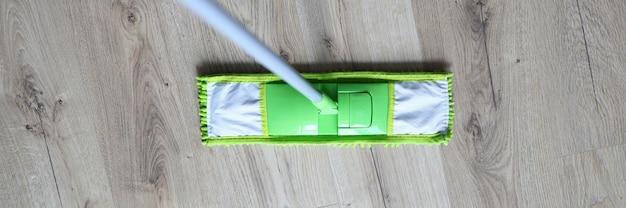 Close-up, desinfecção de piso laminado em pé com esfregona. execute a limpeza úmida do apartamento. desinfecção após doenças infecciosas. limpeza antibacteriana durante a pandemia. alojamento limpo em quarentena