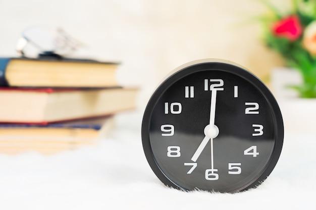 Close-up despertador preto com livro sobre a mesa