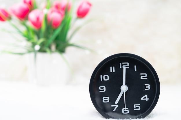 Close-up despertador preto com um buquê de flores em um vaso na mesa