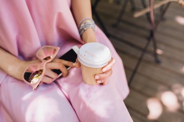 Close-up detalhes das mãos da mulher sentada no café em roupa de moda verão, vestido de algodão rosa, óculos de sol, bebendo café, acessórios elegantes, vestuário moderno e relaxante