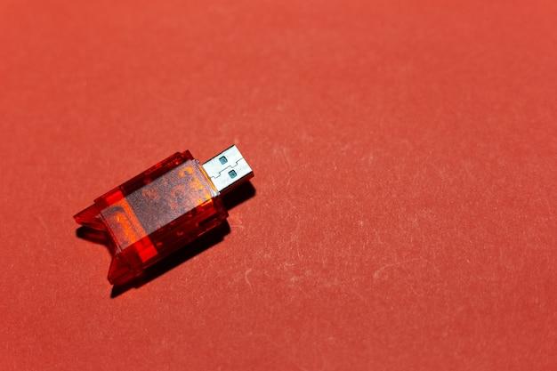 Close-up do adaptador flash usb para cartão sd, isolado em um fundo de cor vermelha.