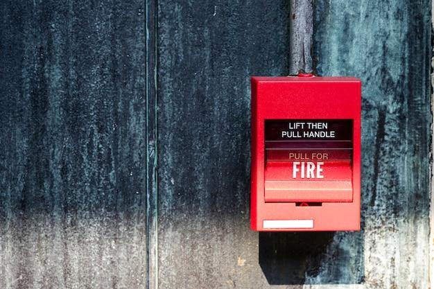 Close up do alarme de incêndio vermelho no uso da parede para acidente de incêndio.
