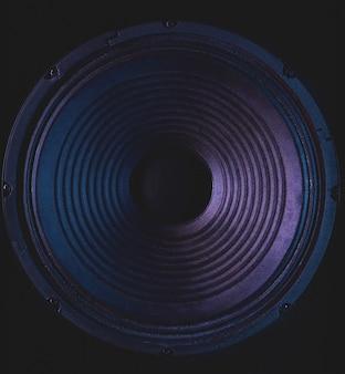 Close-up do alto-falante estéreo em fundo preto.