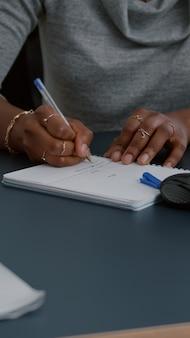 Close-up do aluno com pele negra, escrevendo a lição de casa de comunicação no notebook enquanto está sentado na mesa na sala de estar. mulher jovem estudando matemática na plataforma de e-learning fazendo lição de casa durante o ensino médio