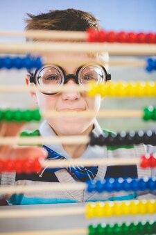 Close-up do aluno olhando através do ábaco na sala de aula