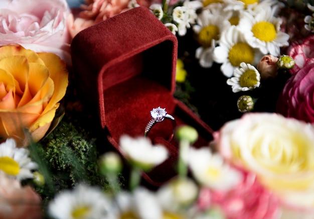 Close-up do anel de casamento na caixa vermelha com decoração de arranjo de flores