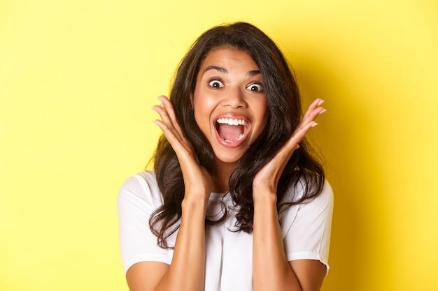 Close-up do animado modelo feminino afro-americano, ofegando e parecendo espantado, levantando as mãos e vendo algo legal, em pé sobre um fundo amarelo.