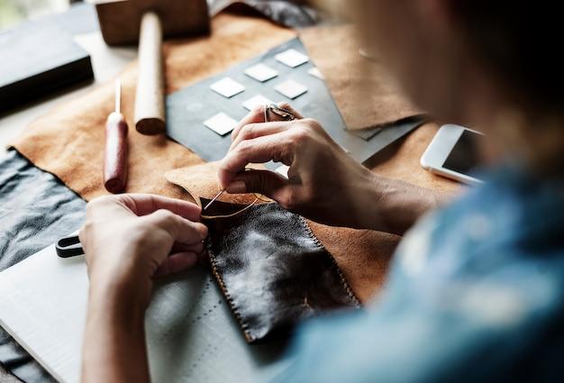 Close up do artesanato de couro de costura de artesão