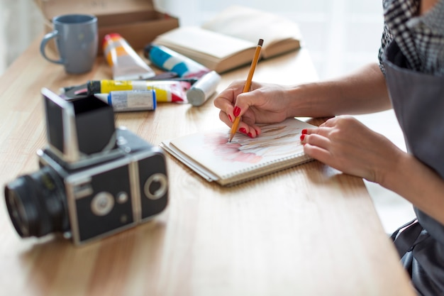 Close-up do artista trabalhando na mesa e câmera