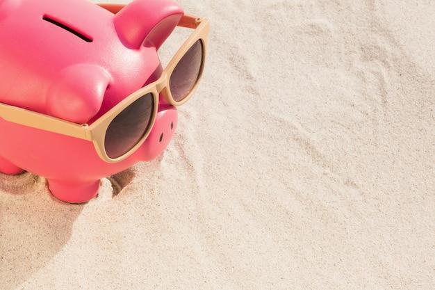 Close-up do banco piggy com óculos de sol mantido na areia