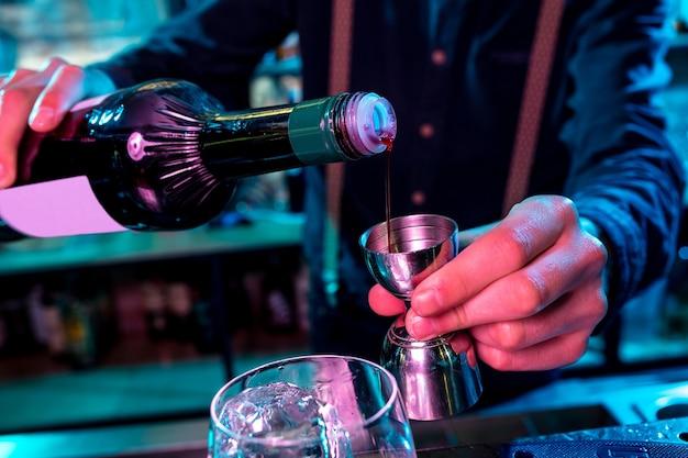 Close-up do barman preparando um coquetel alcoólico com luz de néon multicolorida