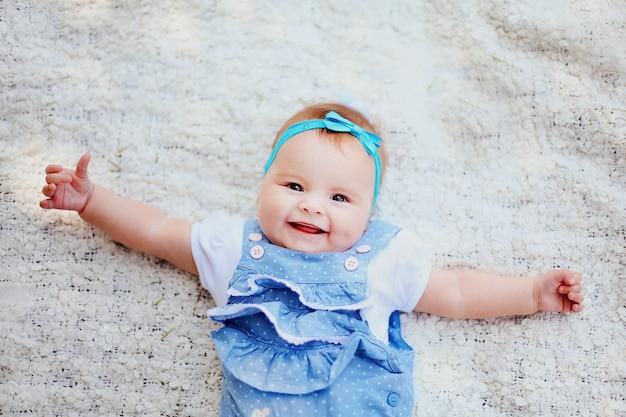 Close up do bebê de sorriso bonito com olhos grandes. criança pequena bonito feliz que tem o divertimento no jardim com família. doce menina