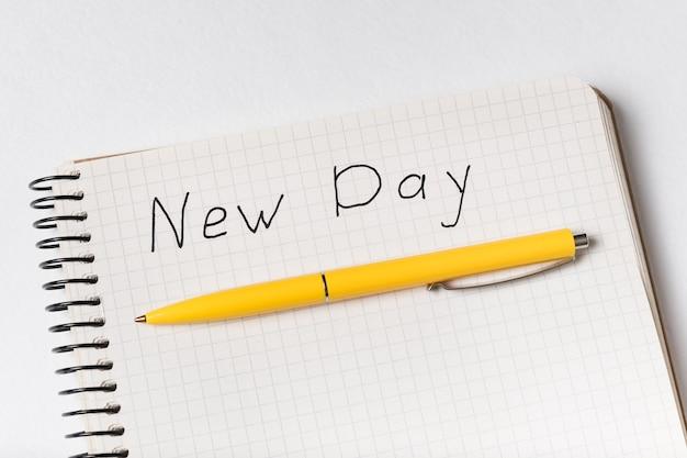 Close-up do bloco de notas com palavras novo dia e caneta. inscrição manuscrita no caderno.